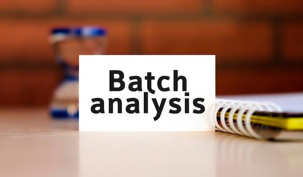 Testo di analisi batch su foglio bianco con blocco note e clessidra