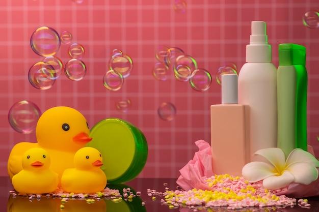 Accessori da bagno paperelle di gomma, gel doccia e shampoo, sale marino, fiori sullo sfondo