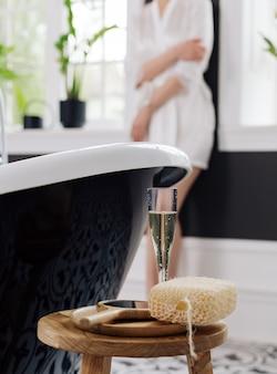 Accessori da bagno su un tavolo vicino alla vasca da bagno e un bicchiere di champagne