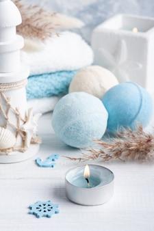 Bombe da bagno con fiori secchi, candele aromatiche accese e asciugamani