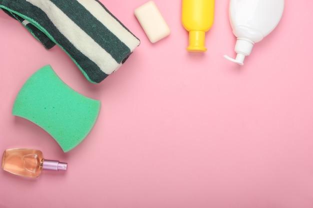 Prodotti da bagno per la cura della bellezza del corpo, igiene. asciugamano, spugna, sapone, shampoo per bottiglie su un pastello rosa