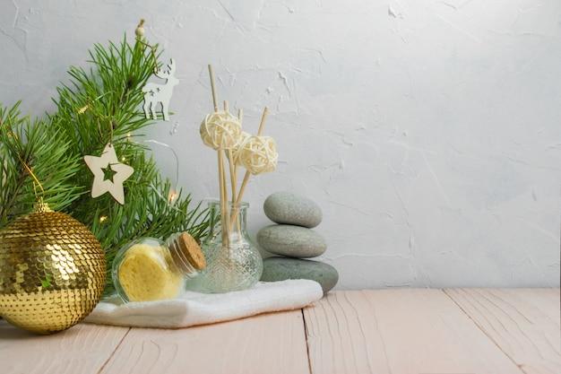 Sale da bagno e bastoncini aromatici con pietre spa su una mensola in legno