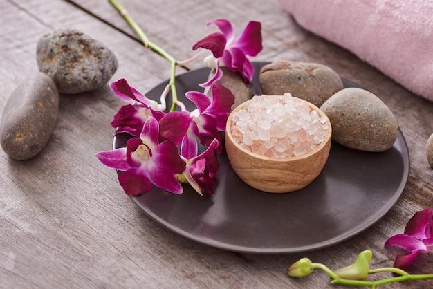 Sale da bagno alla ciotola di bambù e fiori di orchidee su legno scuro