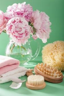 Bagno e spa con fiori di peonia spazzolano asciugamani di spugna