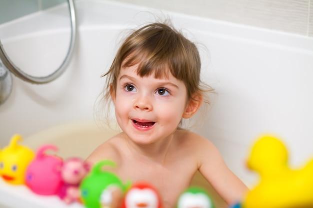 Tempo del bagno. bambina carina che fa il bagno e gioca con i suoi giocattoli mentre è seduta in una vasca da bagno