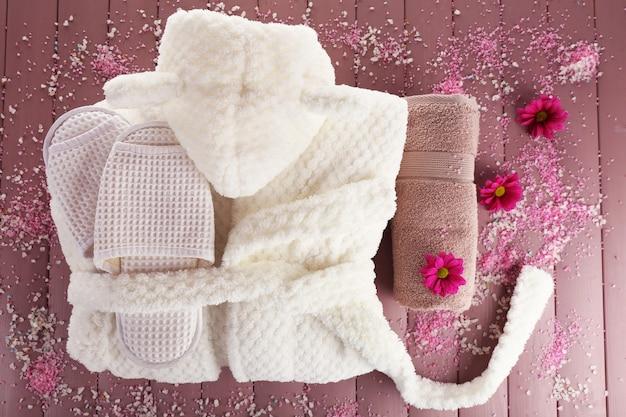 Accappatoio, asciugamano e ciabattine su una superficie di legno, vista dall'alto