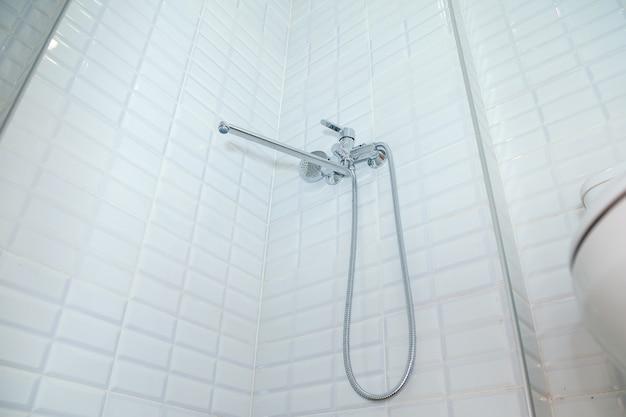 Zona bagno per fare la doccia con rubinetto e soffione su parete piastrellata. il rubinetto della doccia in metallo sporge dalla parete. vista dal basso. spazio di copyright per il testo