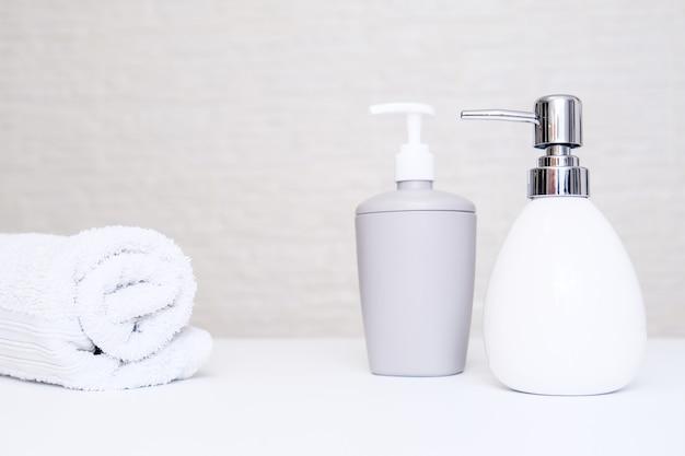 Sfondo del bagno, accessori da toilette per la cura delle mani e del corpo, distributore di sapone liquido e asciugamani su sfondo chiaro.