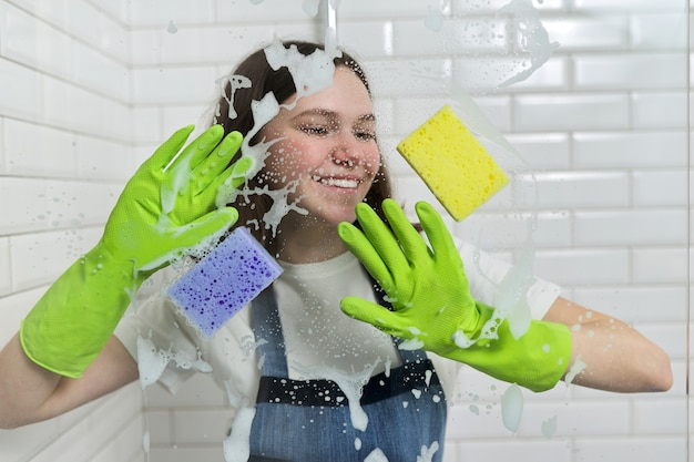 Pulizia del bagno, ragazza adolescente che lava il vetro della doccia con schiuma e spugne, primo piano della mano delle femmine in guanti verdi e spugne colorate