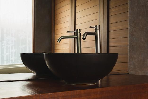 Lavandino nero interno del bagno con rubinetto d'argento e specchio sul piano in legno.