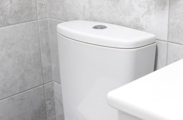 Interno del bagno con foto del primo piano della cisterna del serbatoio della toilette nei colori bianchi