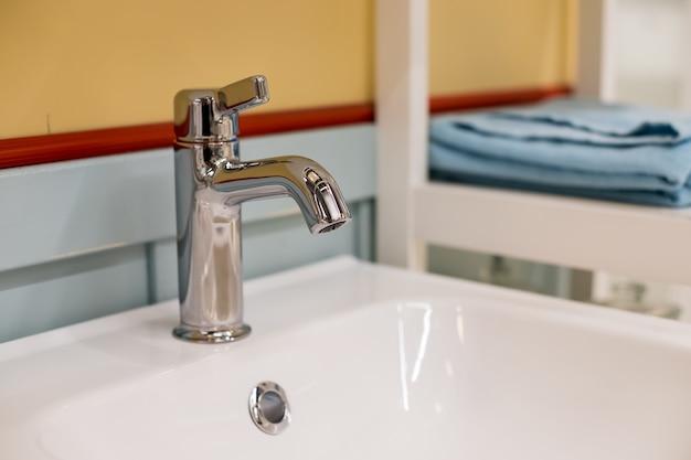 Interno del bagno con lavandino bianco e rubinetto