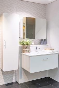 Interno del bagno con pareti bianche, mobili vintage, asciugamani, wc e lavandino