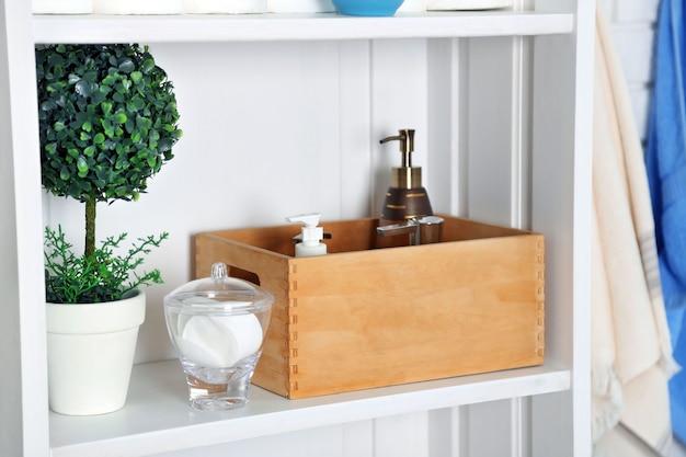Set da bagno con scatola, spugne e dispenser su una mensola in interni chiari