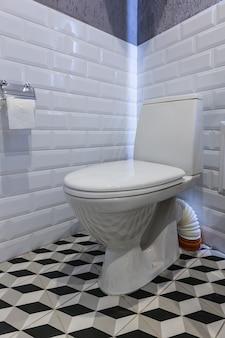 Toilette bianca del bagno con le mattonelle