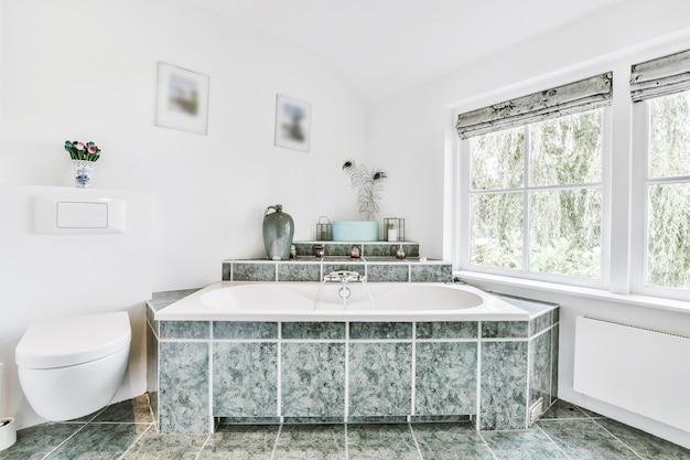 Vasca da bagno e cabina doccia situata sulla parete piastrellata vicino all'armadio con lavandino contro la finestra in casa