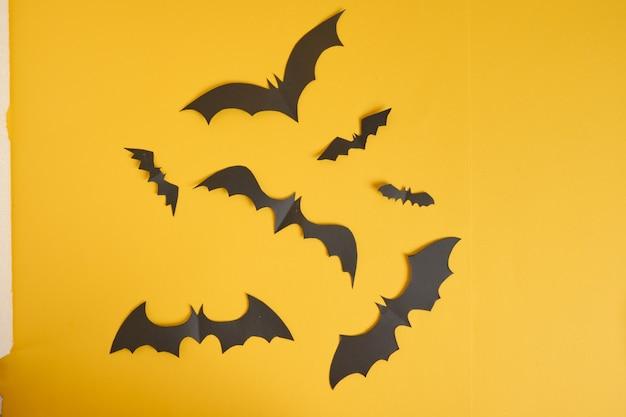Pipistrelli tagliati da carta nera su arancione