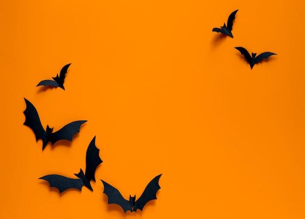 Pipistrelli su sfondo arancione. vista piana laico e dall'alto. Foto Premium