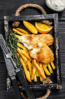 Piatto di pesce e patatine fritte con patatine fritte e salsa tartara in un vassoio di legno. fondo in legno nero. vista dall'alto.