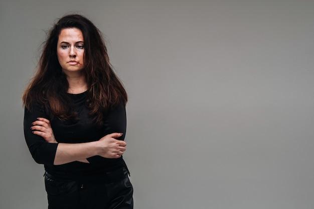 Una donna maltrattata in abiti neri su uno sfondo grigio isolato. violenza contro le donne