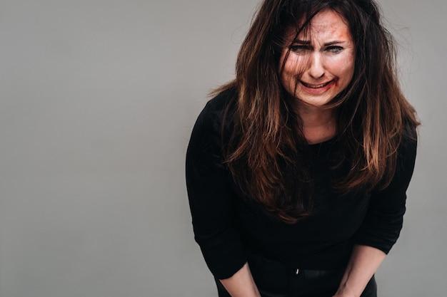 Una donna maltrattata in abiti neri urla su uno sfondo grigio isolato. violenza contro le donne.