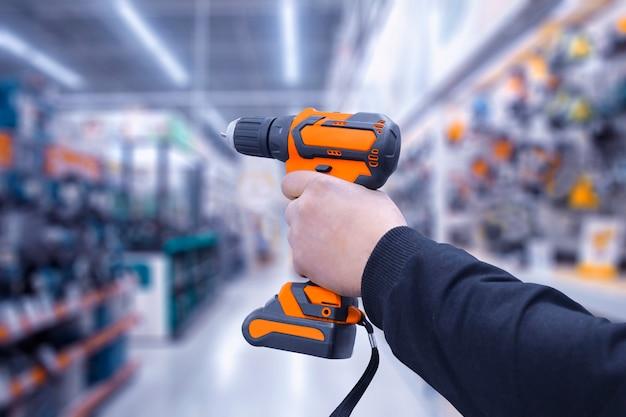 Trapano a batteria o cacciavite in mano, isolato sullo sfondo di un negozio di ferramenta.