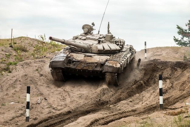 Il carro armato da battaglia esegue esercizi per guidare attrezzature militari su un campo di carri armati