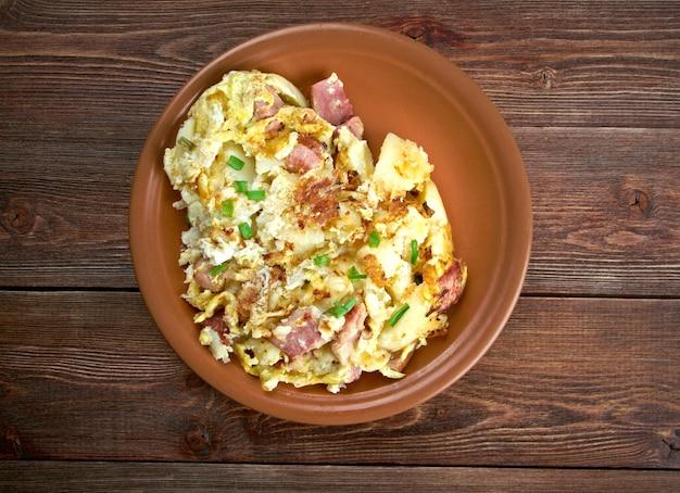 Bauernfruhstuck la colazione del contadino. piatto per la colazione di campagna tedesca a base di patate fritte, uova, cipolle, porri e pancetta o prosciutto