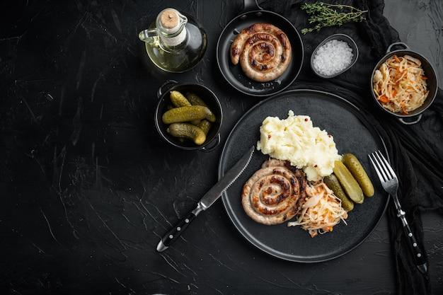 Salsicce fritte bavaresi su crauti, su sfondo nero, vista dall'alto laici piatta, con spazio per il testo copyspace