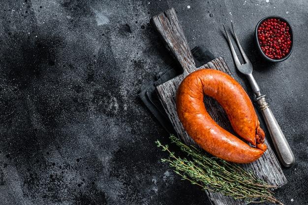 Salsiccia affumicata bavarese su una tavola rustica in legno con timo. sfondo nero. vista dall'alto. copia spazio.