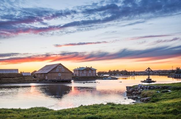 Baia della prosperità sulle isole solovetsky, una croce di legno e un edificio della stazione biologica sotto un bellissimo cielo al tramonto