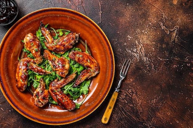 Ali di pollo di bufalo barbecue su un piatto con rucola. sfondo scuro. vista dall'alto. copia spazio.