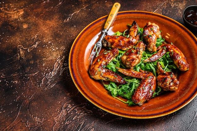 Ali di pollo di bufalo barbecue su un piatto con rucola. sfondo scuro. Foto Premium
