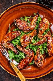 Bbq buffalo ali di pollo su un piatto con rucola. tavolo scuro. vista dall'alto.