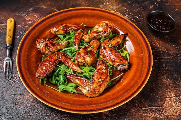 Bbq buffalo ali di pollo su un piatto con rucola. vista dall'alto.