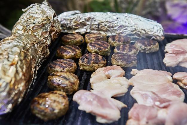 Hamburger al barbecue, cosce di pollo alla griglia festa del fumo al barbecue. avvicinamento.