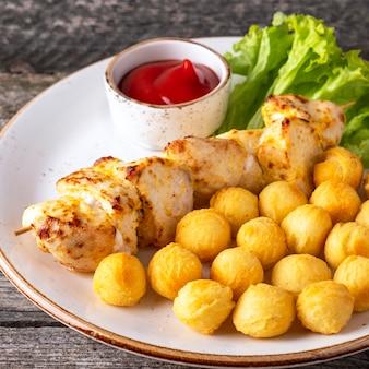 Filetto di pollo alla griglia su spiedini con polpettine di patate