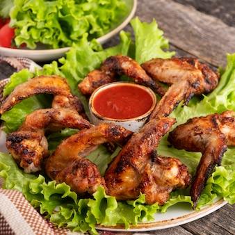 Alette di pollo barbecue guarnire con salsa rossa primo piano