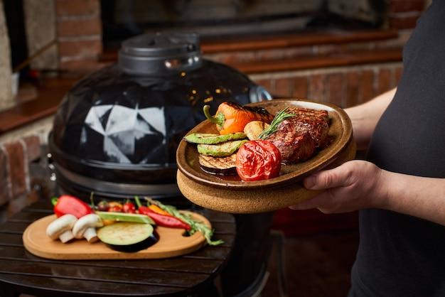 Concetto di cucina barbecue, verdure e carne sfrigolante sulla piastra