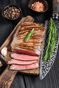 Bistecca di carne di manzo alla griglia su un tagliere di legno