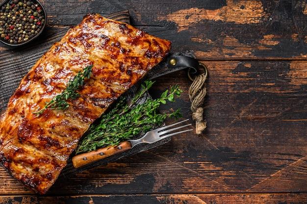 Costine di maiale alla griglia barbecue su un tagliere. fondo in legno. vista dall'alto. copia spazio.