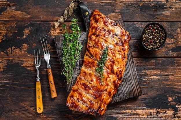 Costine di maiale alla griglia barbecue su un tagliere. fondo in legno. vista dall'alto.