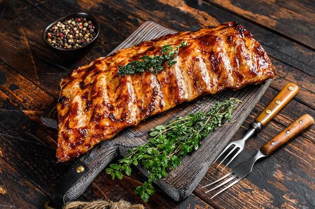 Costine di maiale alla griglia barbecue su un tagliere.