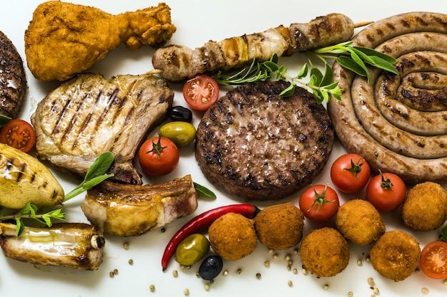 Festa con carne alla griglia con diversi tipi di carne: hamburger di manzo, costolette di maiale, polpette di tacchino, cosce di pollo impanate con patate e pomodori, spezie ed erbe aromatiche. menu estivo
