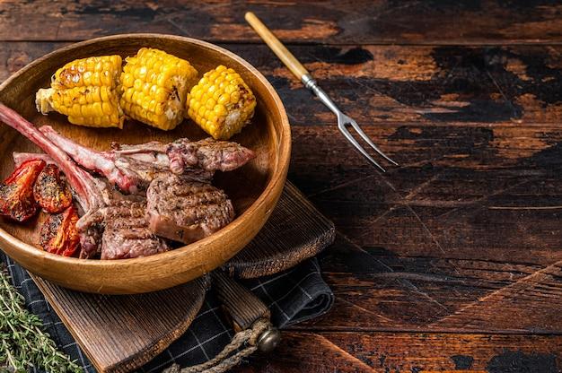 Bistecche di agnello arrosto al barbecue, montone in un piatto di legno. fondo in legno scuro. vista dall'alto. copia spazio.