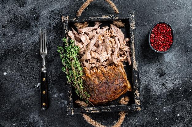 Grigliata di carne di maiale arrosto arrosto in un vassoio di legno. nero