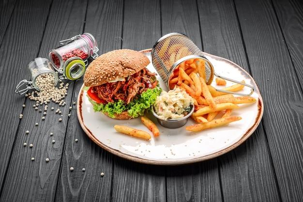 Sandwich di maiale stirato affumicato al barbecue con sottaceti. su una superficie di legno nera