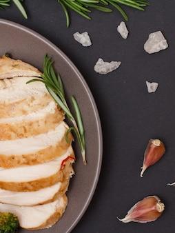 Bprimo piano di petti di pollo al forno o filetto su piastra con rosmarino e aglio su sfondo nero. vista dall'alto.