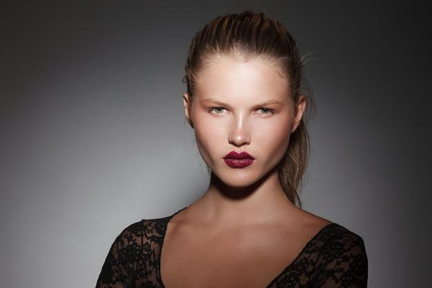 Britratto frontale ravvicinato di una bella ragazza bionda con i capelli raccolti in una coda di cavallo con labbra bordeaux su sfondo grigio scuro.