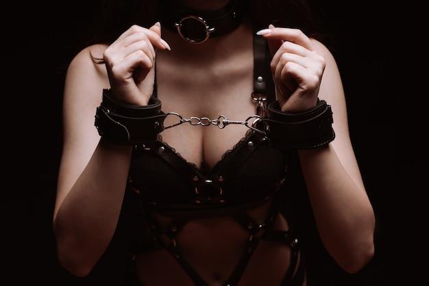 Sadomaso ragazza in manette e biancheria intima sexy in pelle nera da vicino
